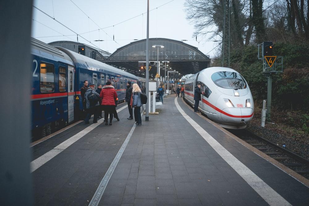 people walking on sidewalk near white and blue train during daytime