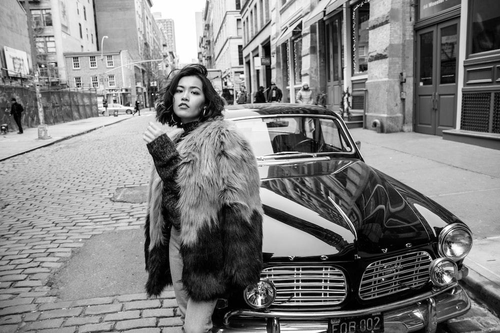 grayscale photo of woman in fur coat standing on sidewalk