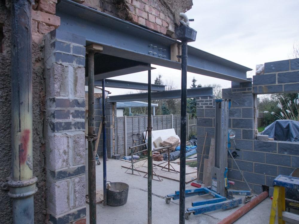 blue metal frame near brown brick wall