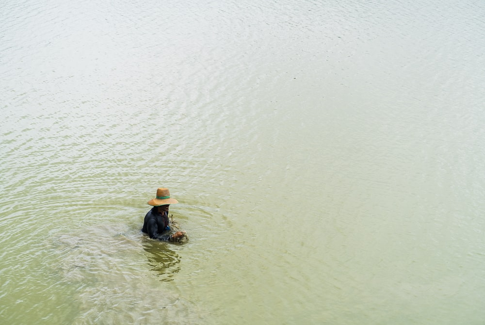 person in black shirt and blue denim jeans on water during daytime