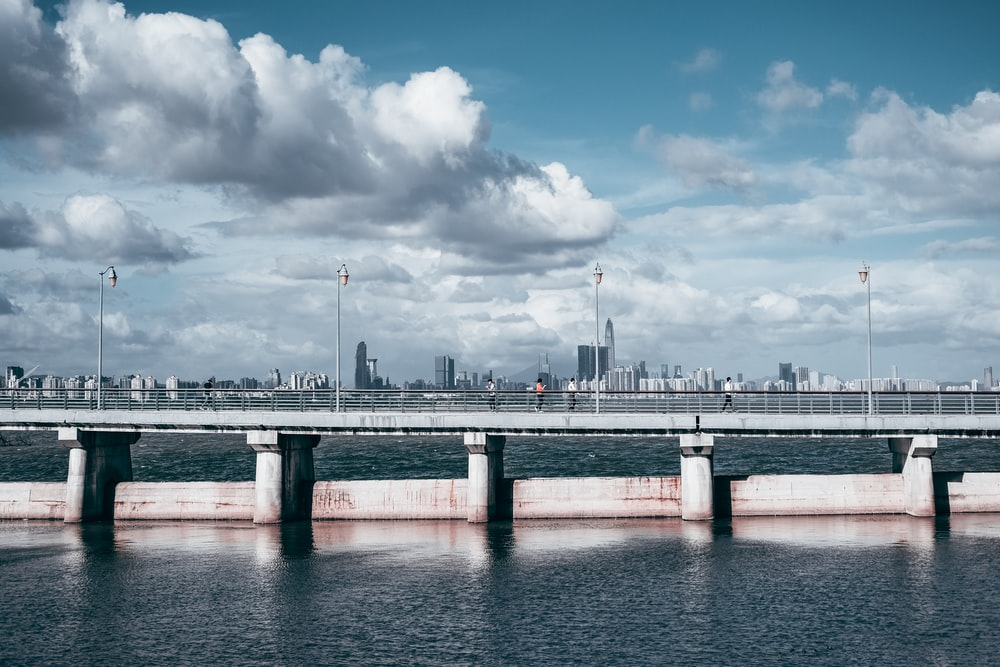 gray concrete bridge under white clouds and blue sky during daytime