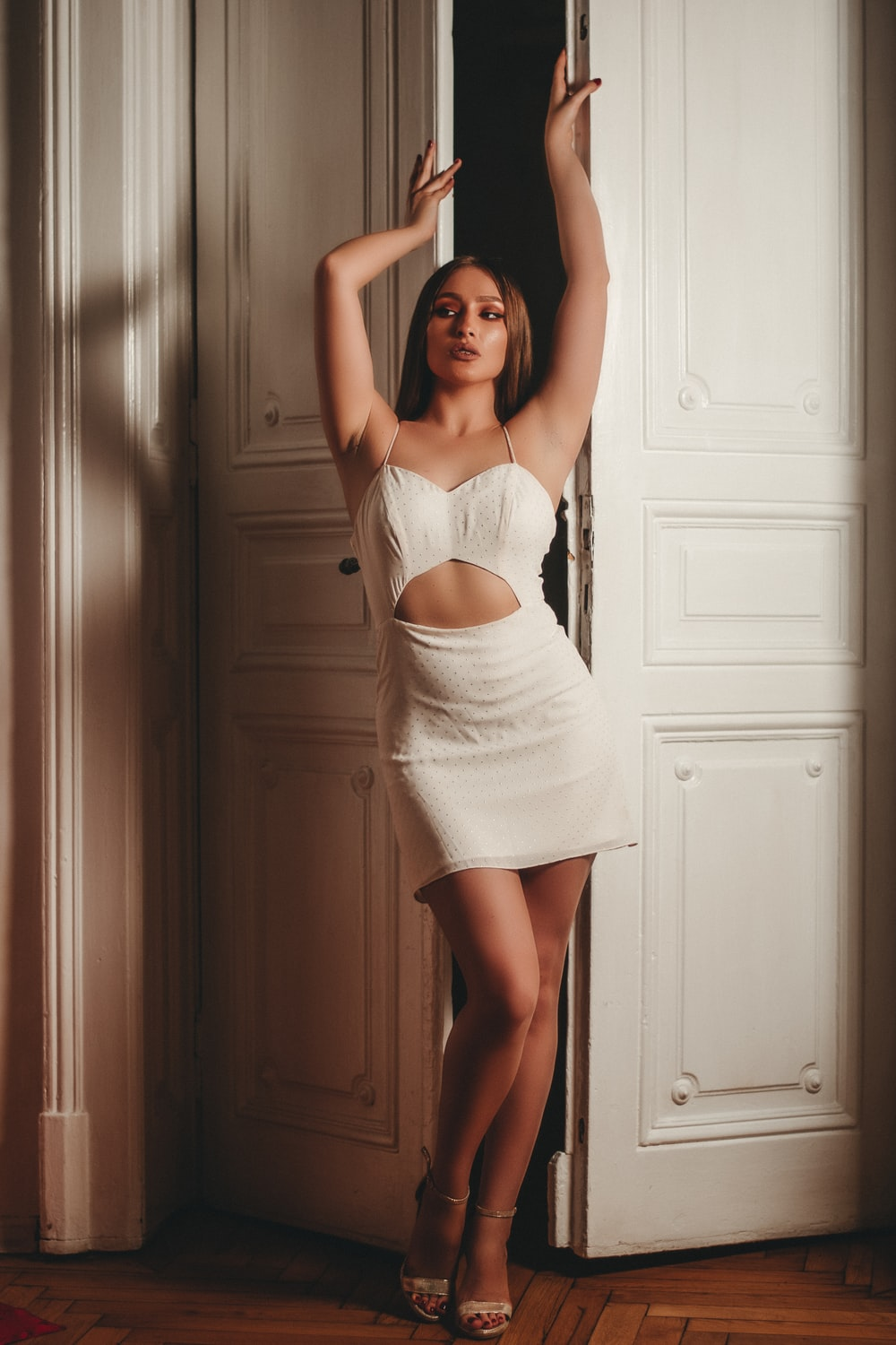 woman in white spaghetti strap top and white skirt standing beside white wooden door