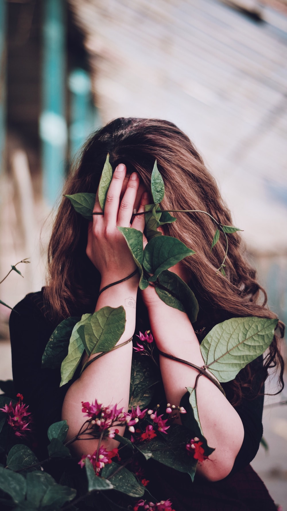 woman covering her face with green leaves