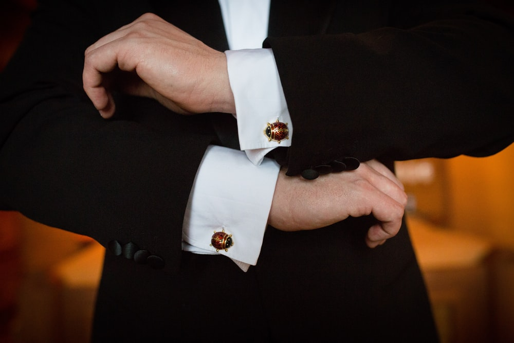 person wearing white dress shirt and black and white beaded bracelet