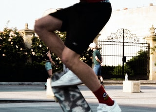person in black shirt and white pants riding skateboard during daytime