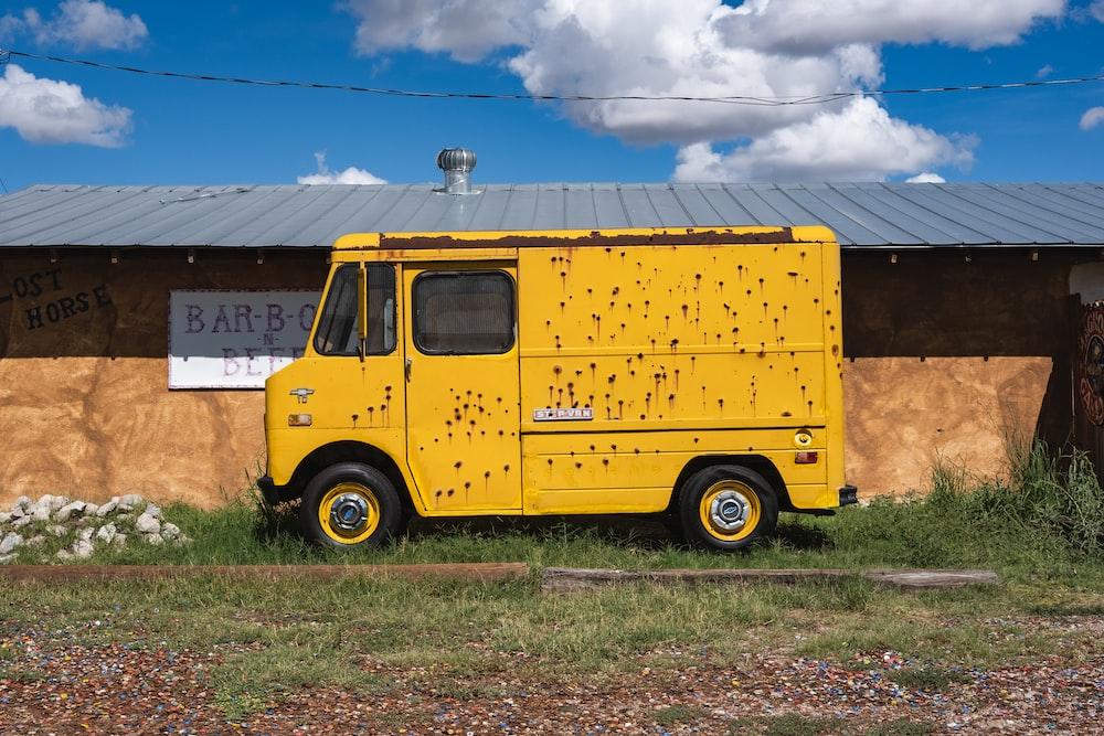 yellow van parked beside brown building