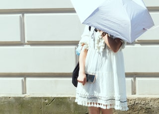 woman in white and blue floral dress holding umbrella