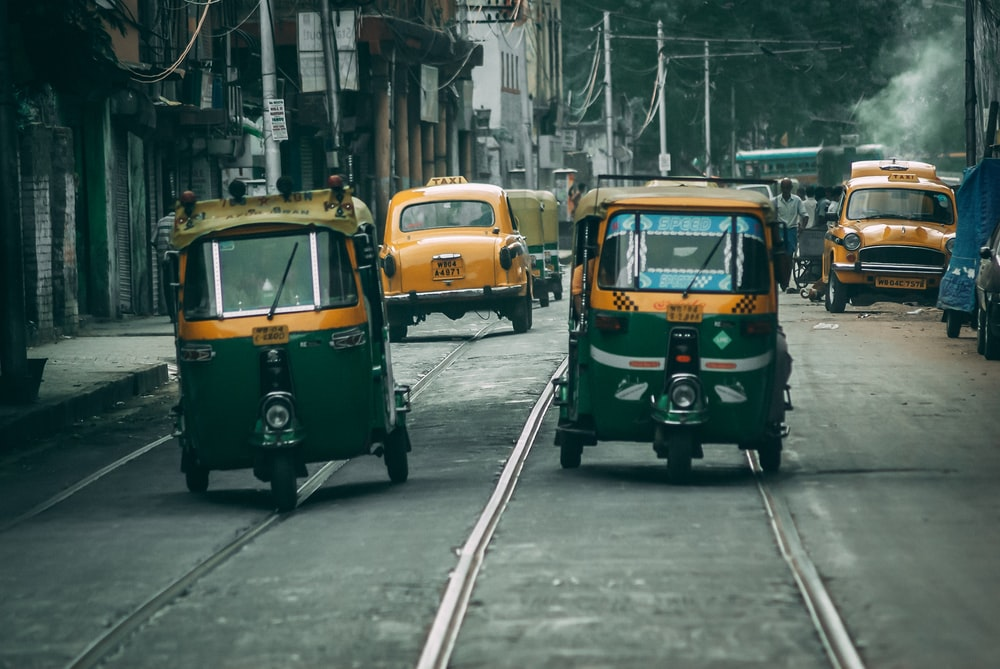 green and yellow auto rickshaw on road during daytime