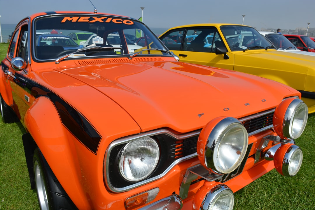 An orange Ford Escort Mexico Mk1 with spotlights at a Ford show.
