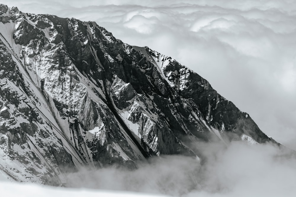 gray and white mountain under white clouds during daytime