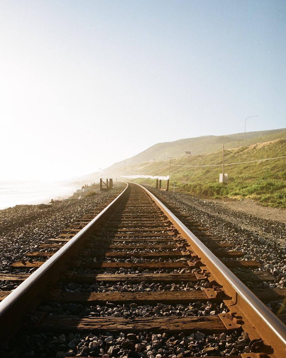 train rail near mountain during daytime