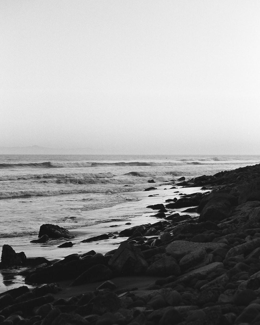 grayscale photo of sea waves crashing on rocks