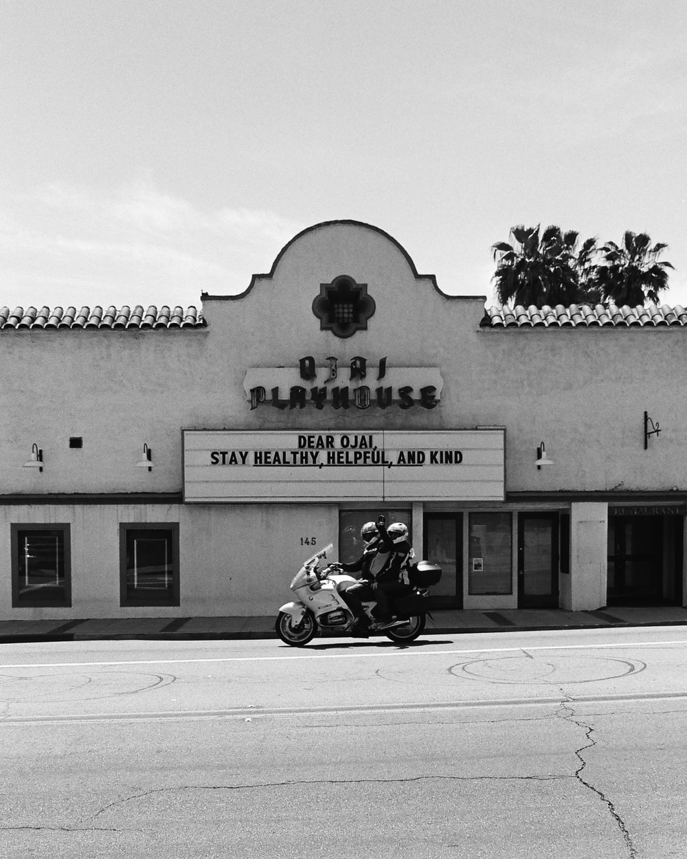 grayscale photo of man riding motorcycle in front of UNKs building
