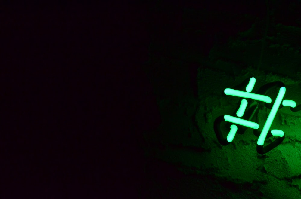 green neon light signage on wall