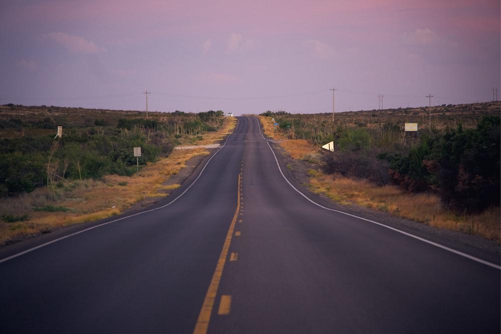 black asphalt road between green grass field under blue sky during daytime