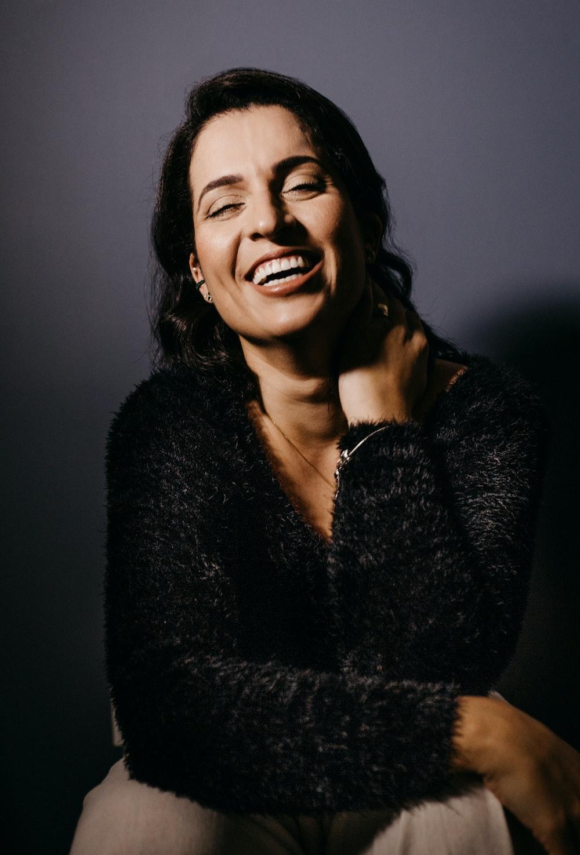 smiling woman in black fur coat