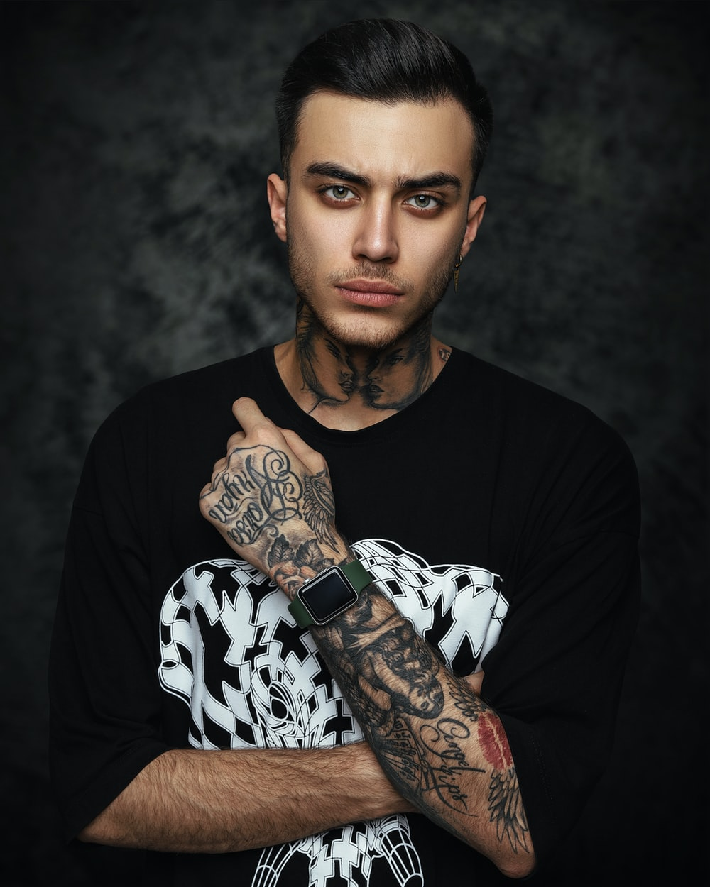 man in black crew neck t-shirt with black and white skull tattoo on his right