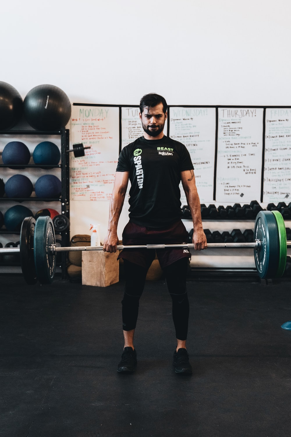 man in black crew neck t-shirt and black shorts carrying barbell