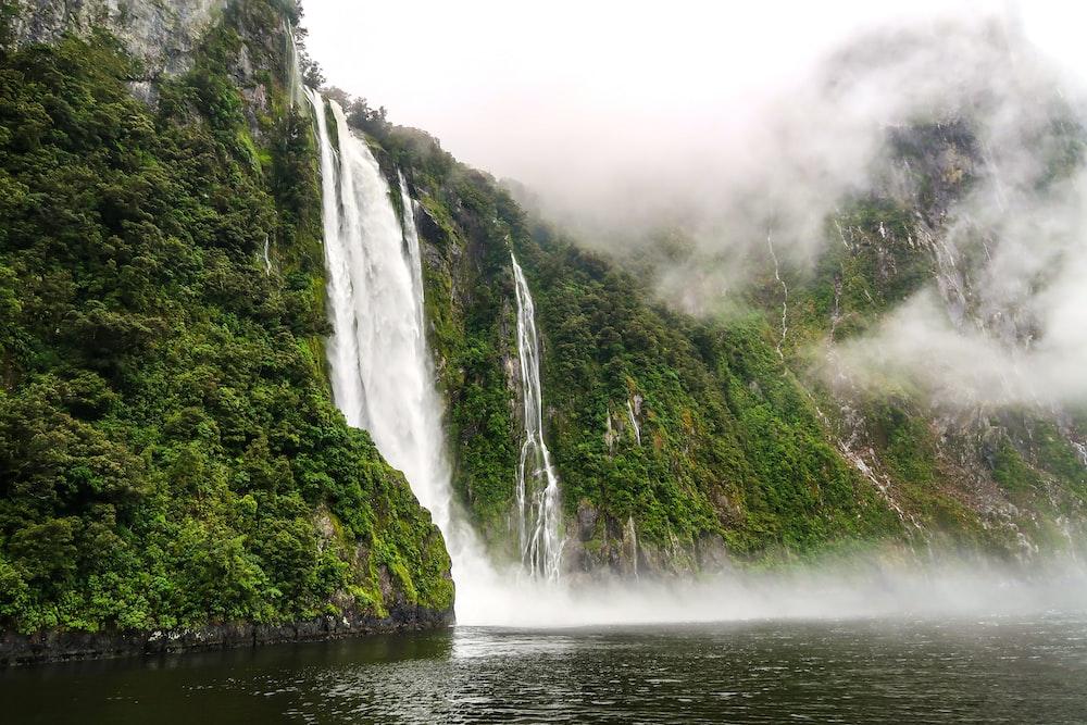 waterfalls on green mountain during daytime