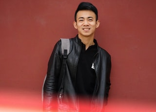 man in black leather jacket standing beside red wall