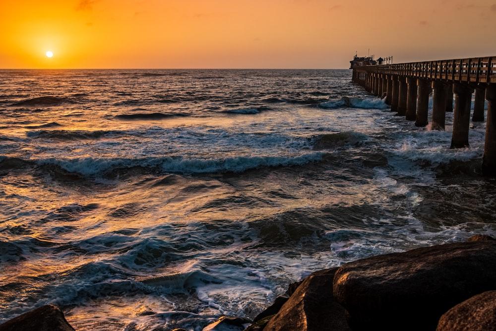 sea waves crashing on brown wooden dock during sunset