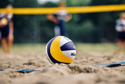 yellow and white volleyball on brown sand during daytime volleyball zoom background
