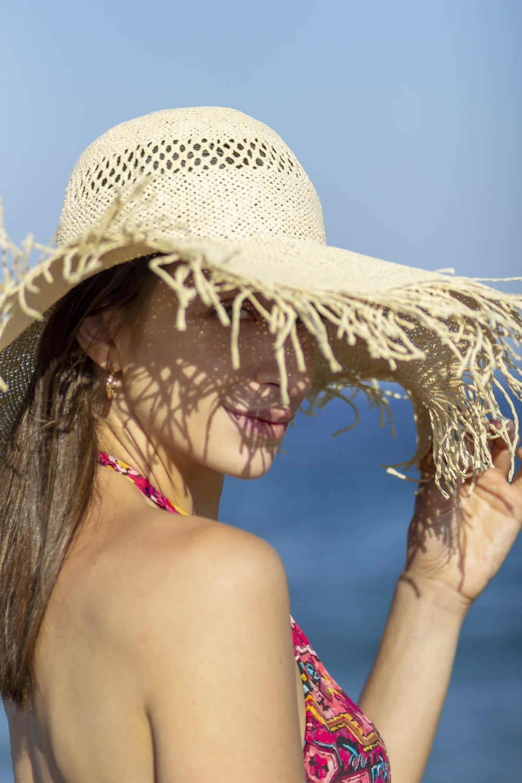 woman in red bikini top wearing brown straw hat