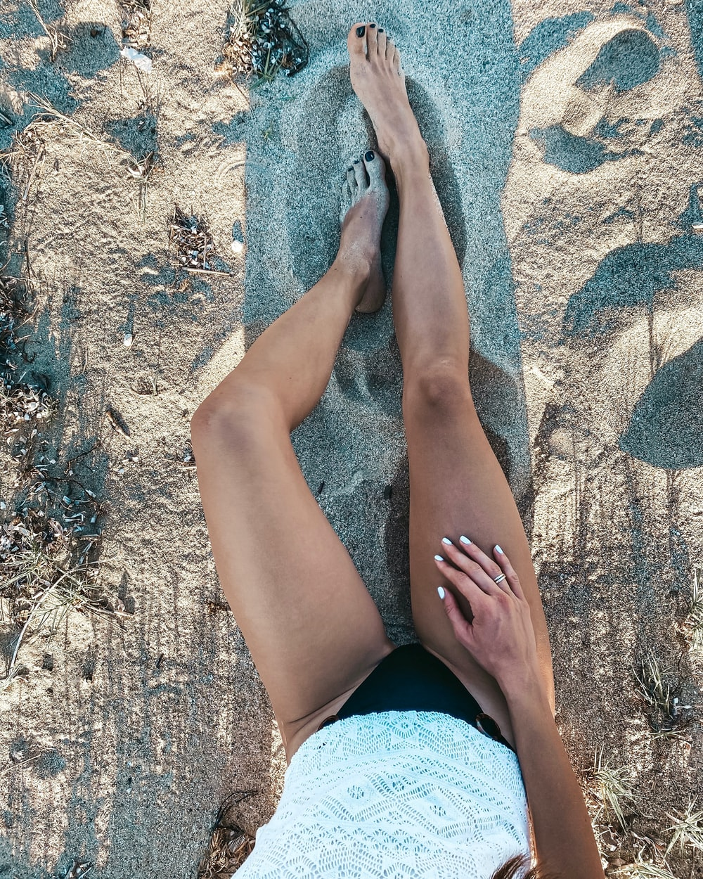 woman in blue denim shorts lying on brown sand during daytime