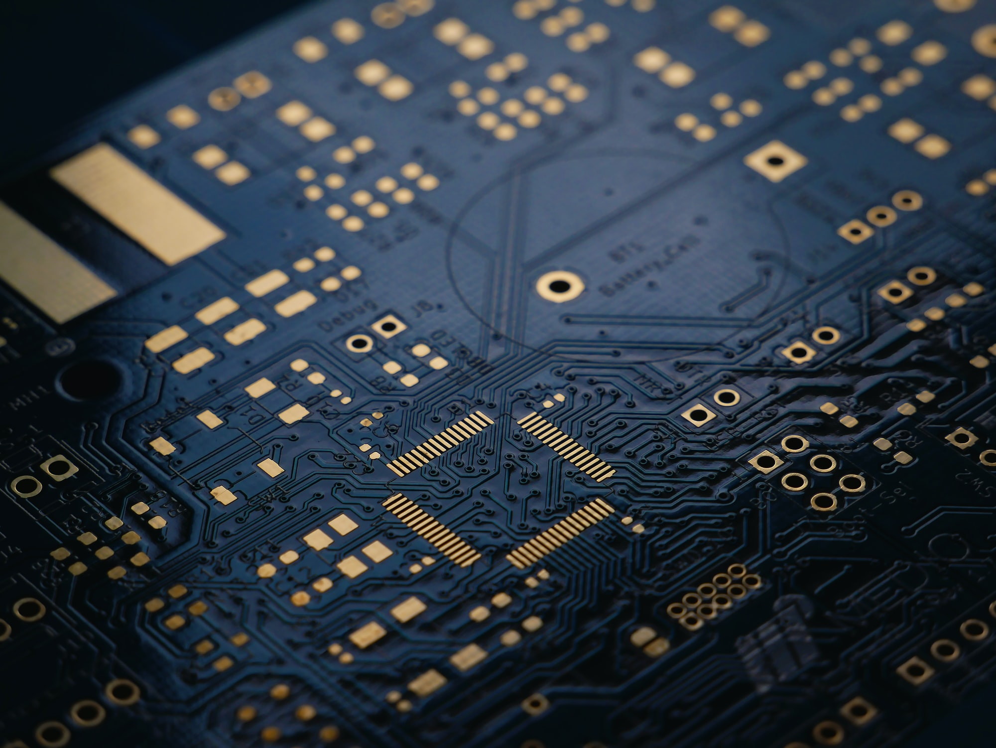 A low exposure photograph of an unsoldered Printed Circuit Board (PCB) with ENIG (Gold) finish.