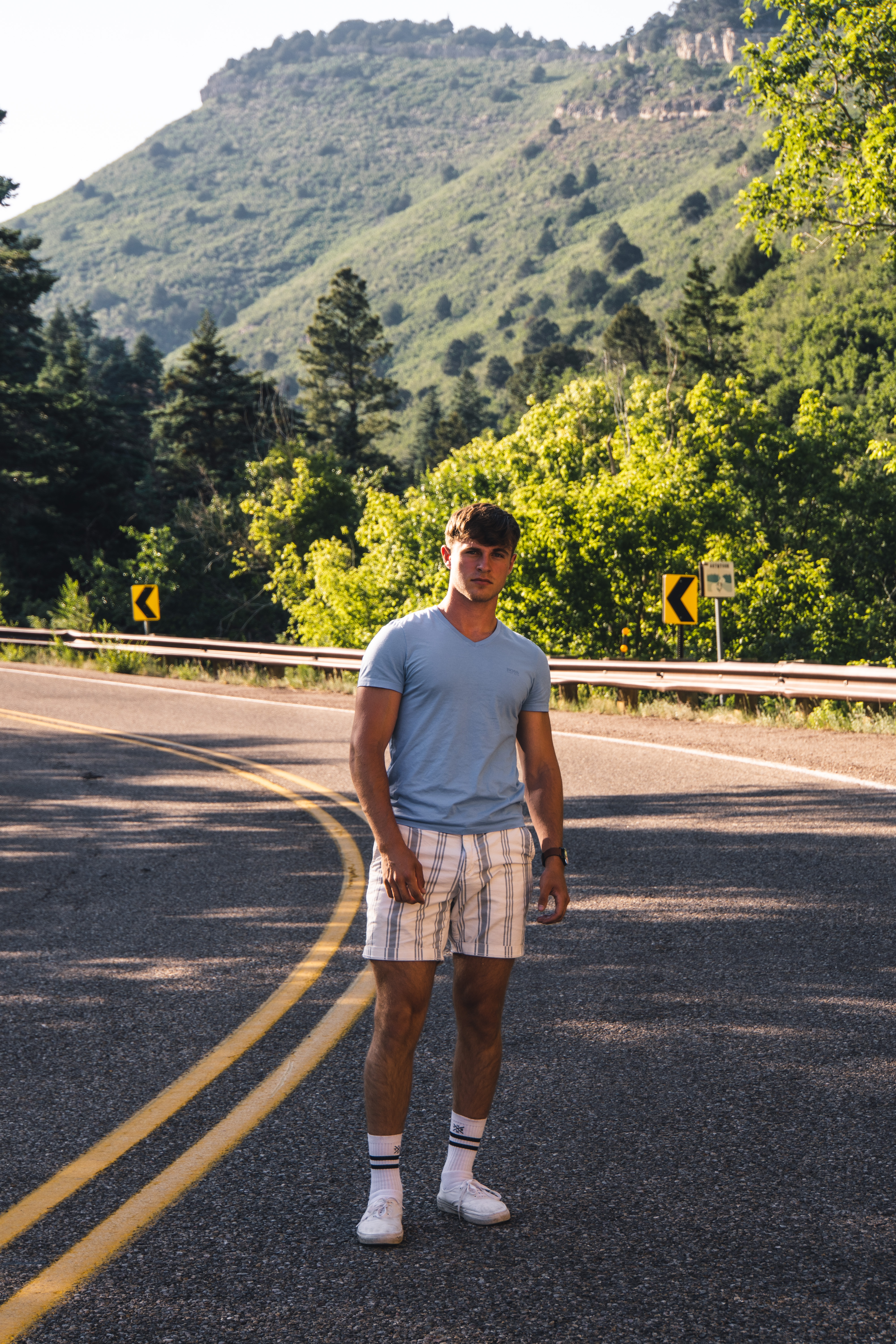 man in white tank top standing on road during daytime