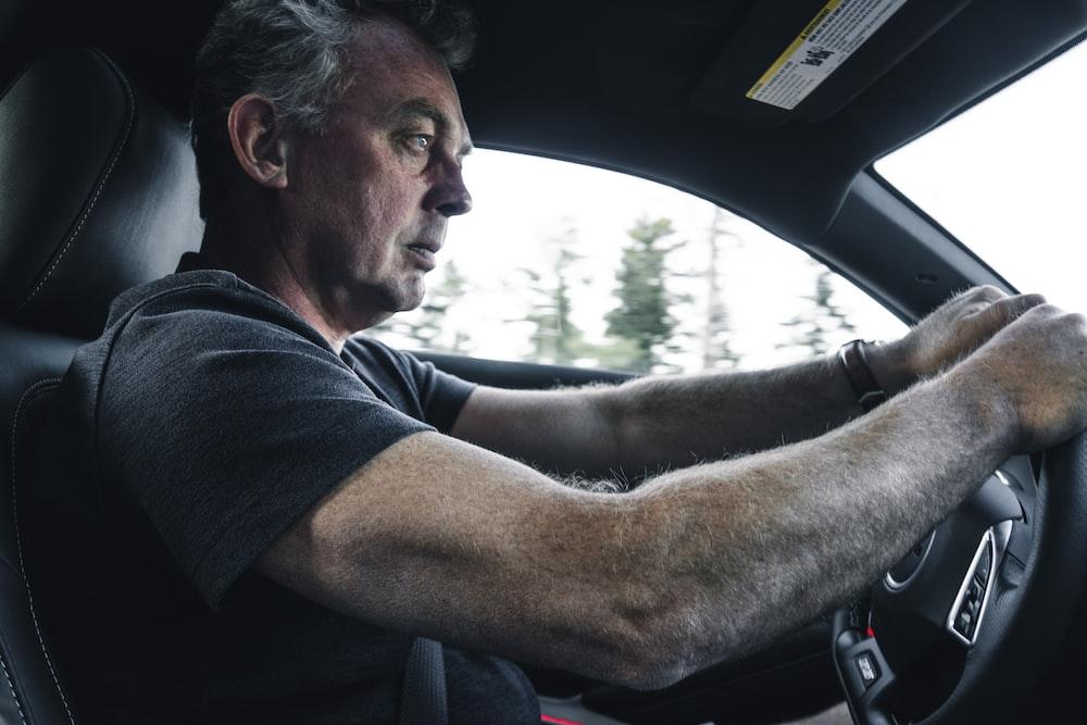 man in black t-shirt driving car during daytime