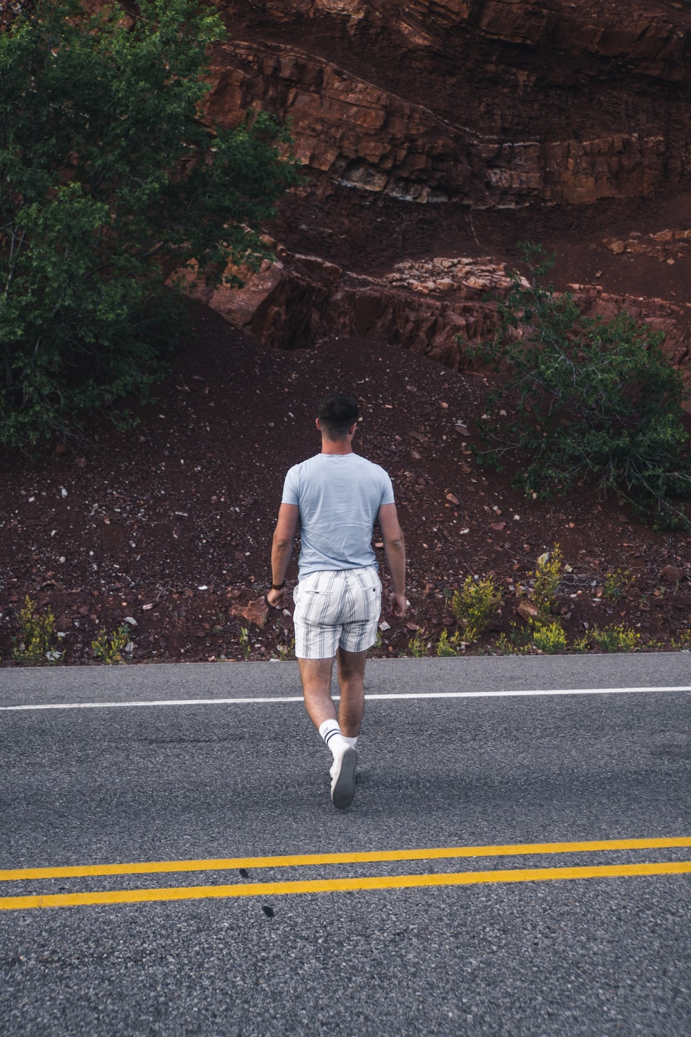 man in white tank top and white shorts standing on road during daytime