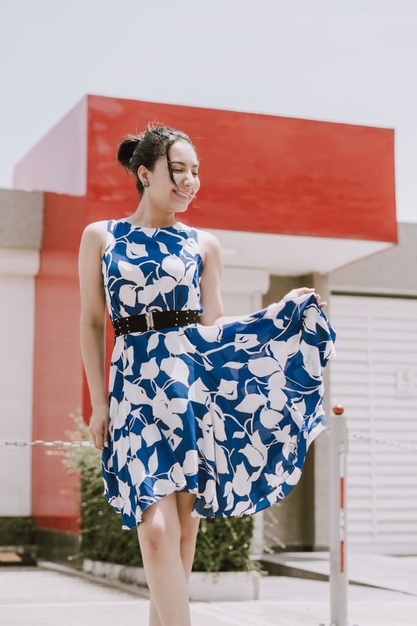 woman in blue and white floral spaghetti strap dress standing near red wall during daytime