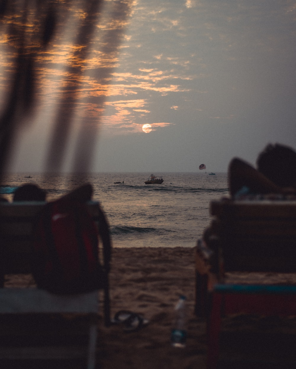 people sitting on brown wooden bench on beach during sunset