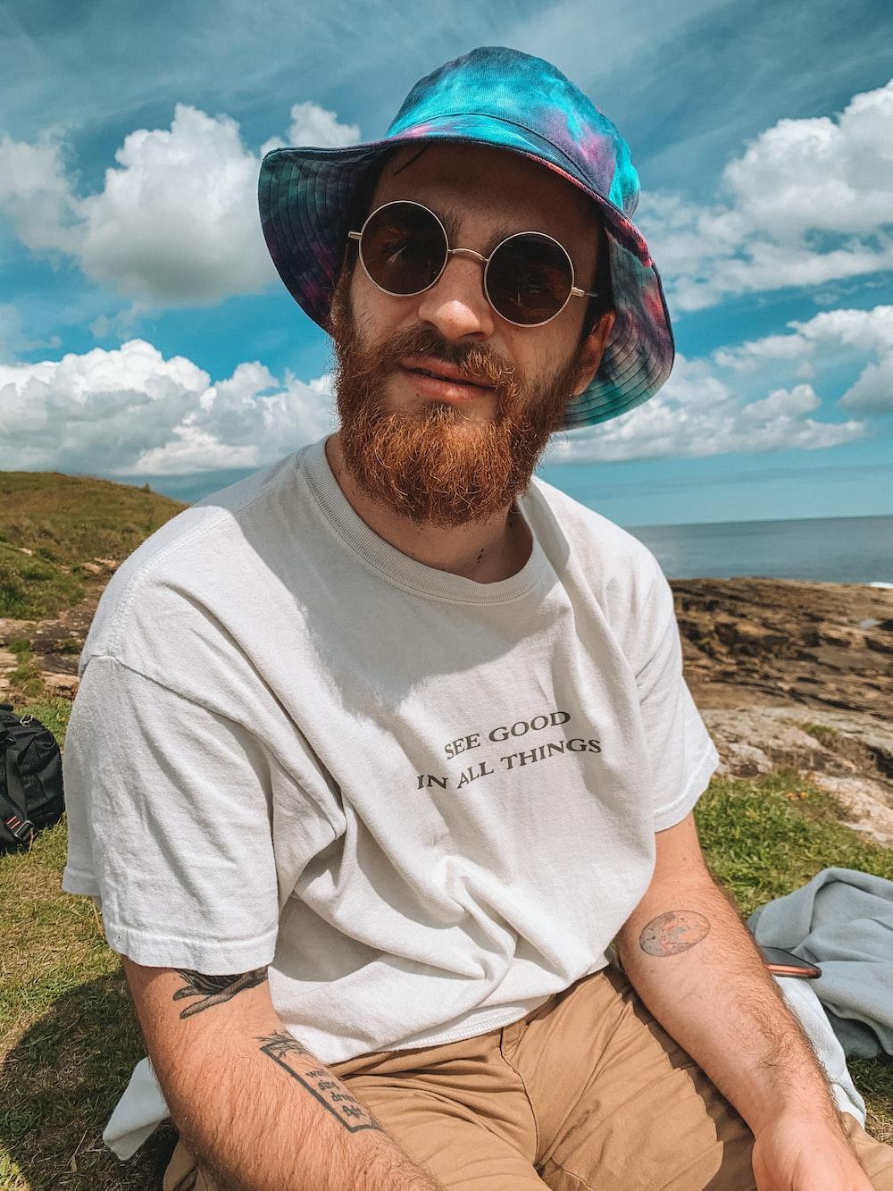 man in white crew neck t-shirt wearing blue sunglasses