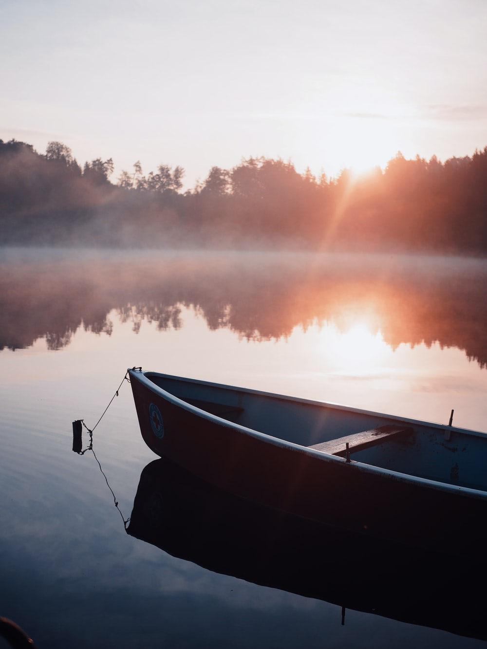 white and black boat on water during sunset