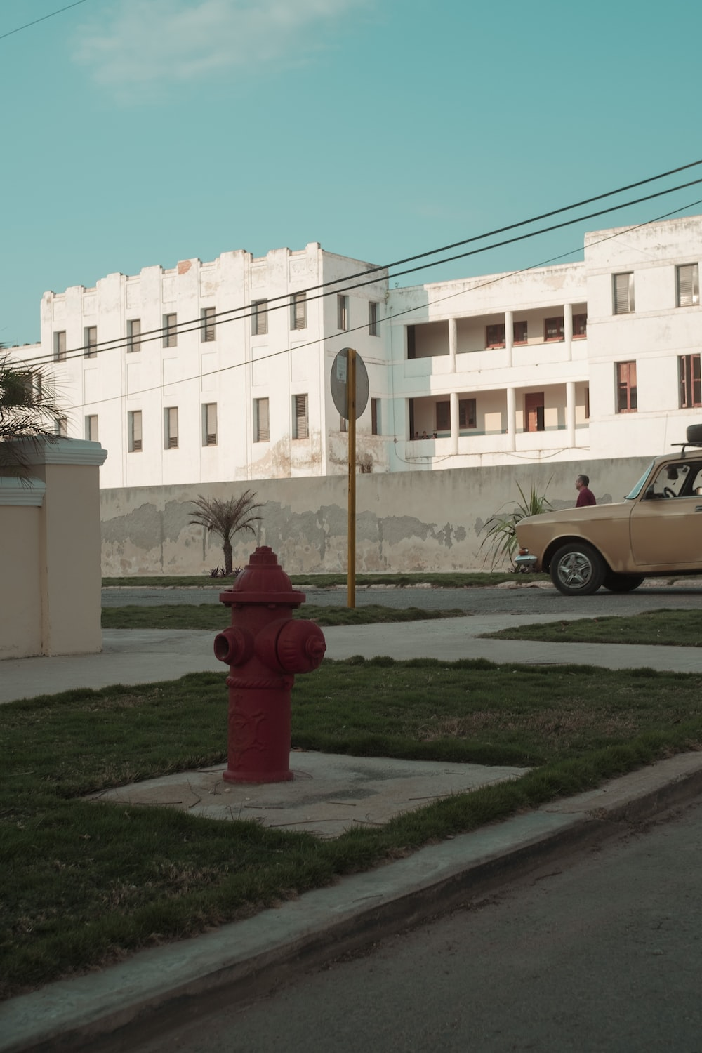 red fire hydrant near white concrete building during daytime
