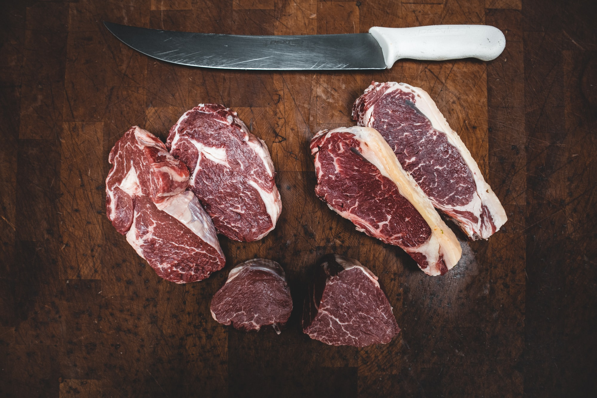 A selection of steaks and a carving knife, arranged on a wooden cutting table.