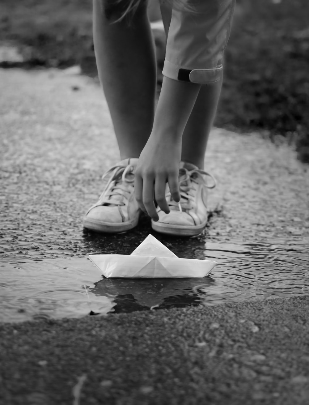 grayscale photo of person in white shorts and sneakers standing on wet road