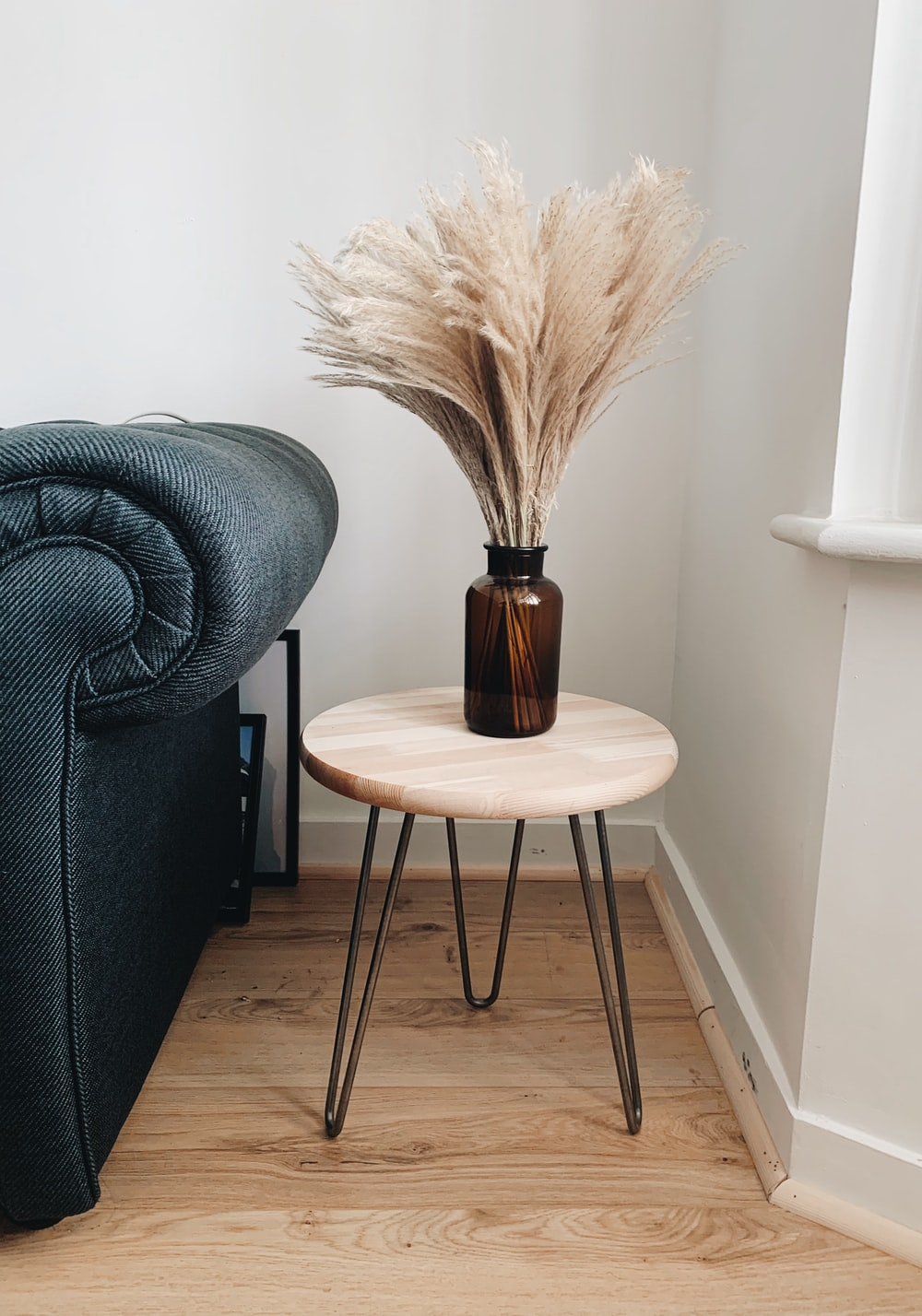 brown wooden round seat beside gray sofa