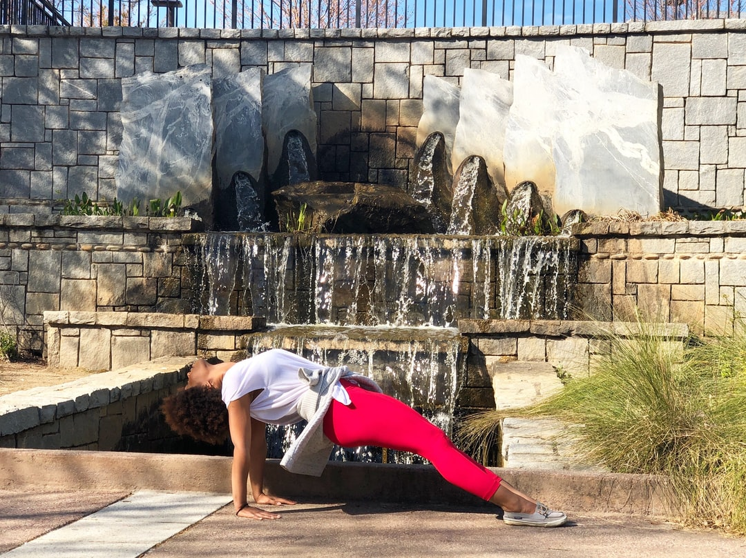 Black woman with an afro practicing Purvottanasana, a yoga pose, in front of a park waterfall. Photo of Christina Mills.