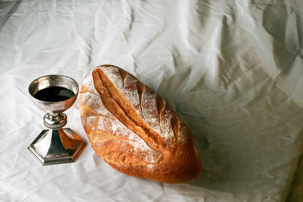 bread on white textile beside clear glass mug
