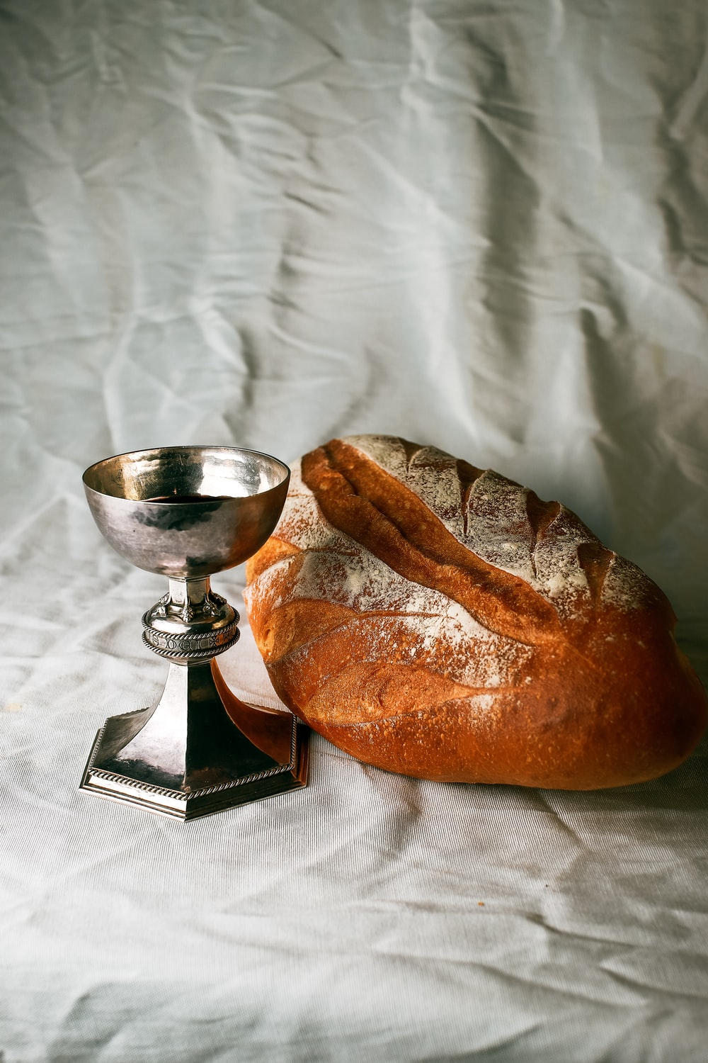 bread on white textile beside stainless steel footed bowl