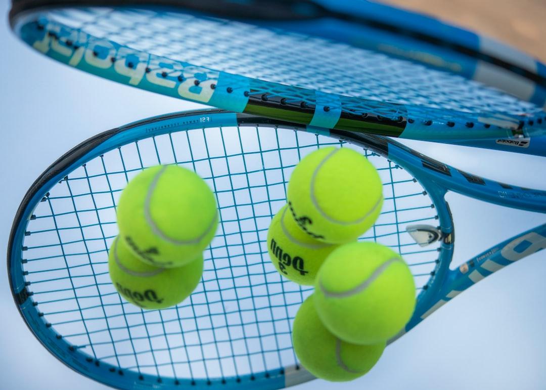 Blue racquet with tennis balls
