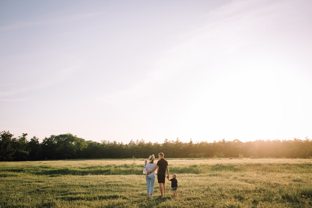 man and woman walking on green grass field during daytime