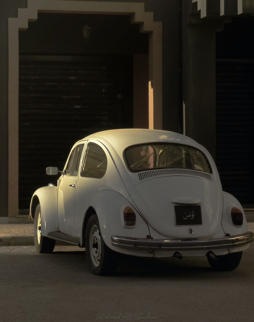 white volkswagen beetle parked beside brown wooden wall