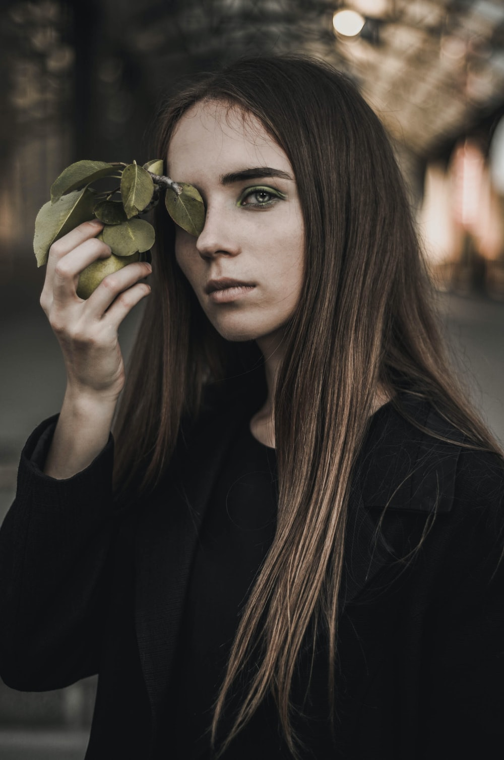 woman in black long sleeve shirt holding green fruit
