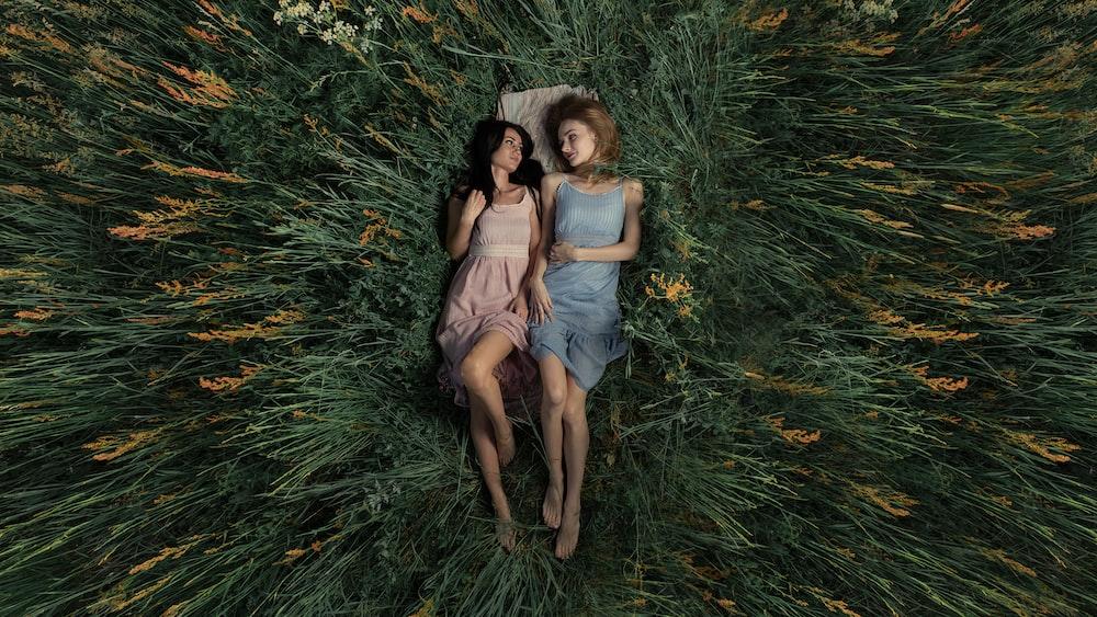 2 women sitting on green grass