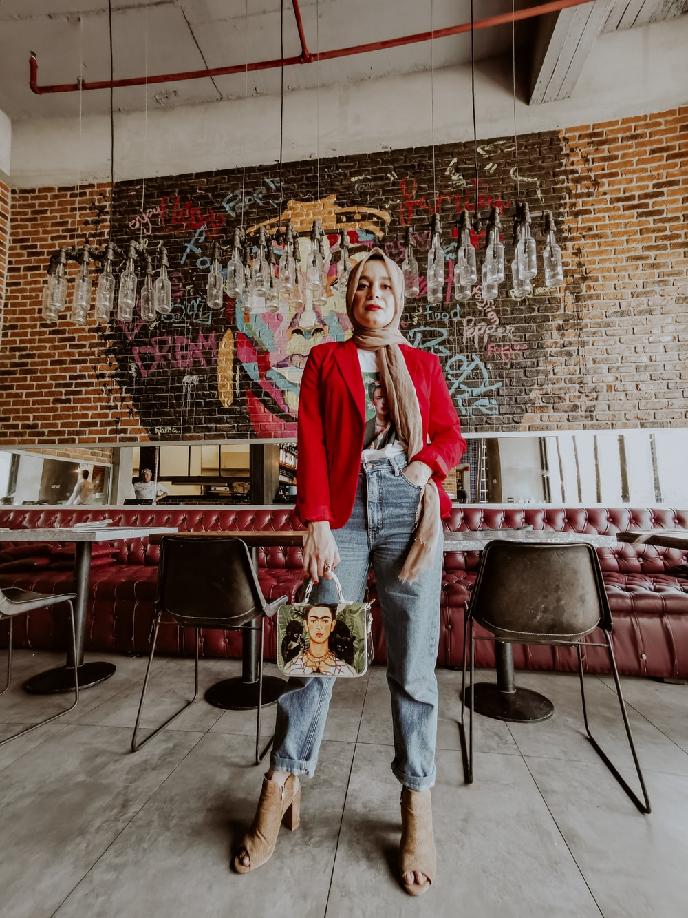 woman in red long sleeve shirt and blue denim jeans standing near red chairs