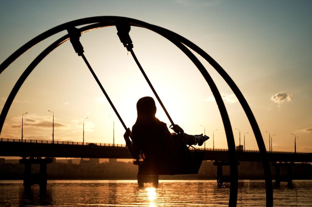 man in black jacket sitting on swing during sunset
